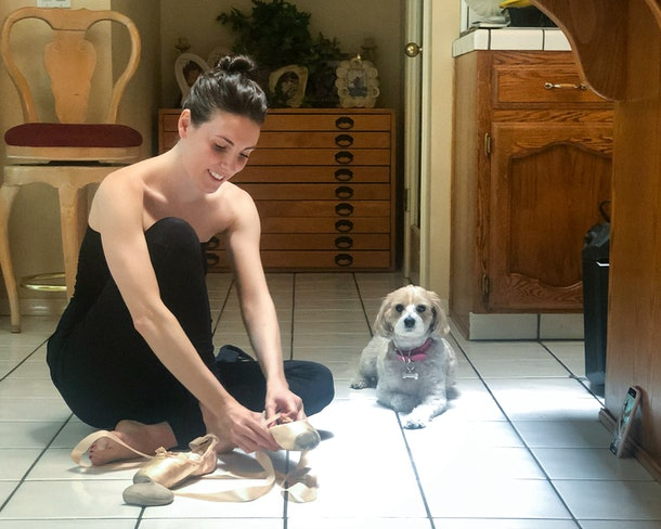 Ballerina Tiler Peck sitting on the floor, putting on her pointe shoes. Her little white dog, Cali, is sitting next to her.