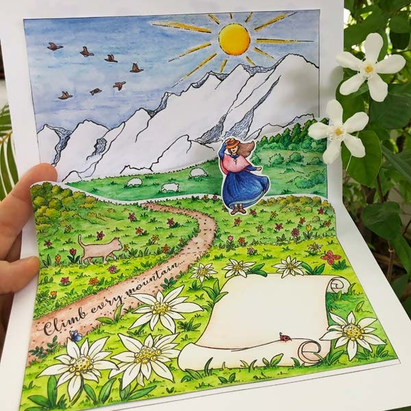 "A brightly colored pop-up card with flowers, a trail with script written upon it reading ""climb every mountain,"" a woman wearing a dress while holding her hat, and a cheeky little cat."