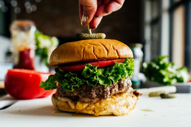 cheeseburger with cocktail pickle on top