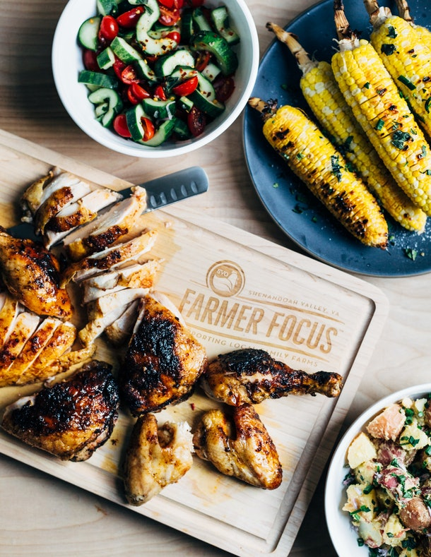 Grilled spicy paprika chicken beside grilled corn.