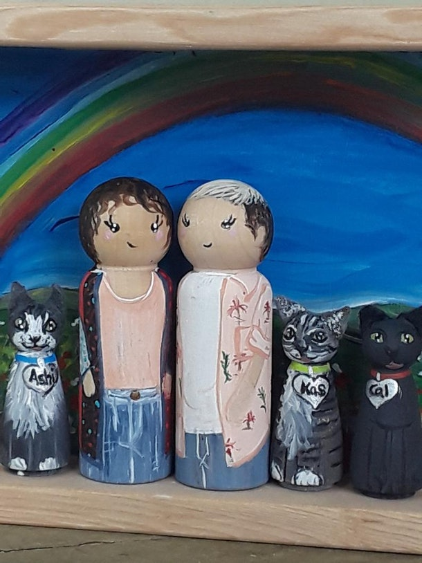 Two peg doll people are displayed with three peg doll cats with a rainbow and landscape background.