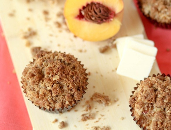 A picture of a perfect, crumbly muffin and a half of a peach.