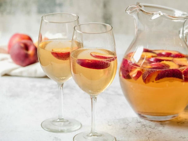 Two glasses and a pitcher full of peach sangria.