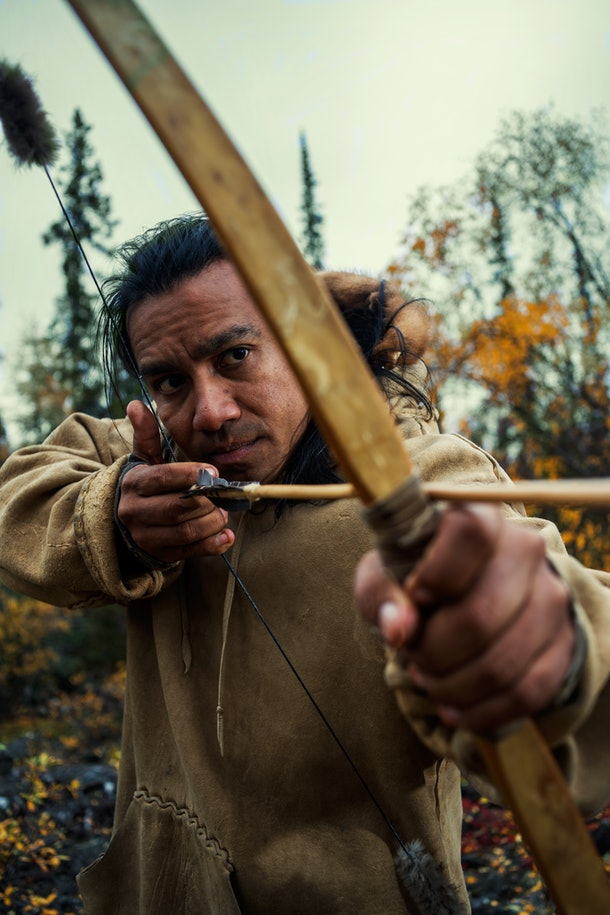 Amós Rodriguez pulls a bow and arrow taut, ready to fire.