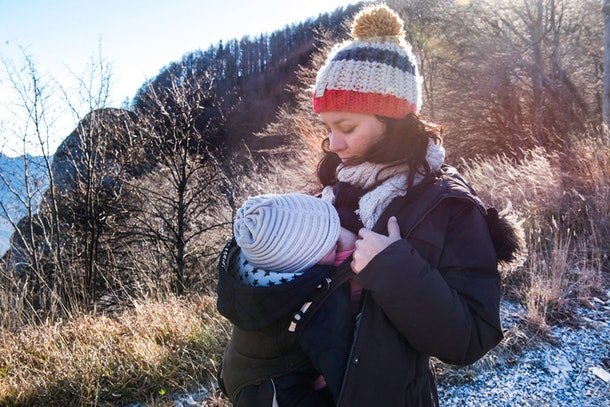 Mom breastfeeding baby in a baby carrier when it's cold outside