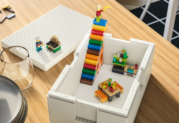 The medium sized Bygglek storage box with the lid beside it, and minifigure chef cooking over the Ikea LEGO stove.