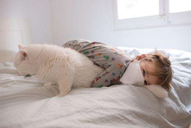 Boy in mask cuddling with cat