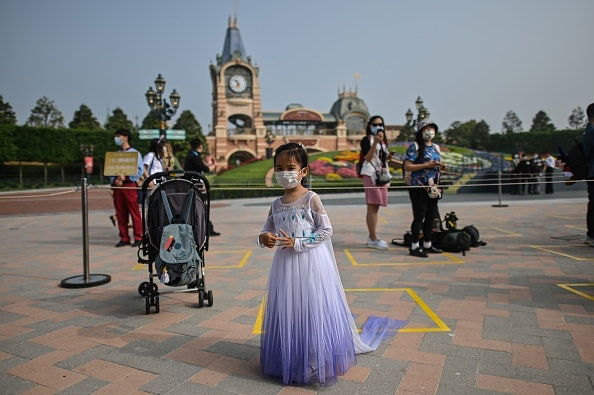 young girl wearing mask and princess dress at theme park