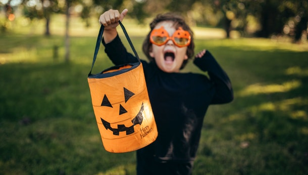 little boy dressed up for halloween with halloween pail
