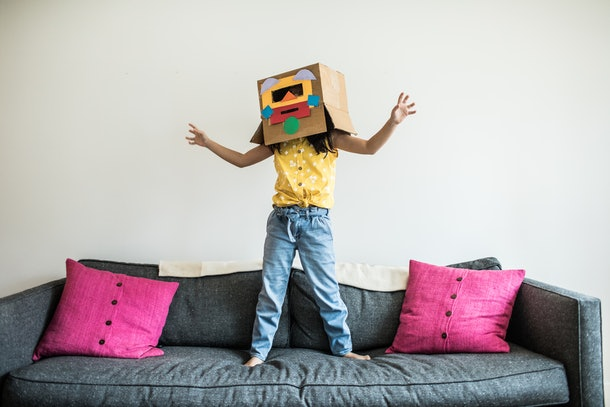 child playing on couch in robot costume