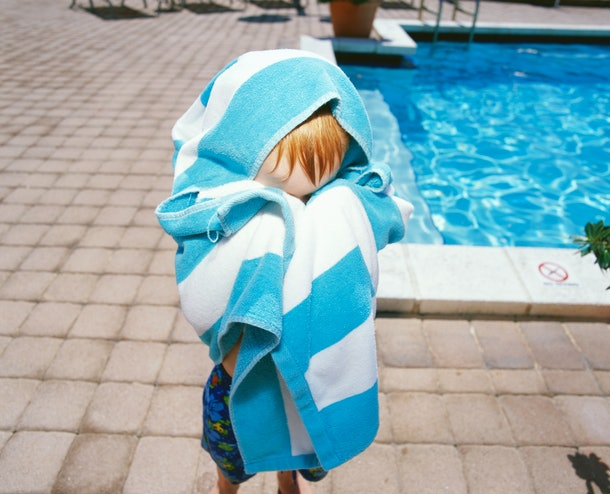 child hiding behind towel