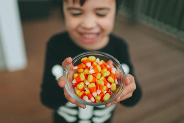 A little boy holding halloween candy.