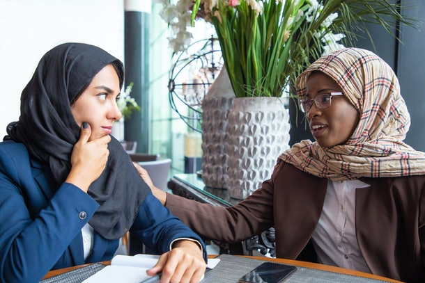 Serious African American employee supporting colleague. Muslim businesswomen chatting in coffee shop. Corporate relationship concept