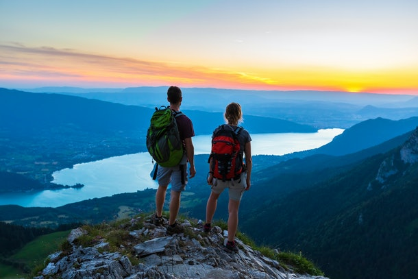 Hikers enjoying scenic view of valley with lake at sunset, couple enjoying summer outdoor trek in mountains, active lifestyle, two people