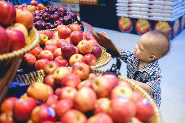 A toddler stands at an apple display at a grocery store, holding fruit and smiling.