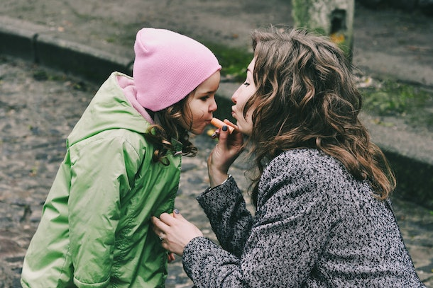 Mother and daughter. Mama put lip balm on daughters lips. Happy family. Amazing, laughing women. Happy mother's day. Casual lifestyle. Rainy spring day. First girls lipstick.