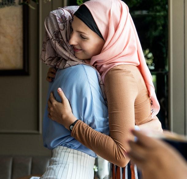 Islamic women friends hugging.