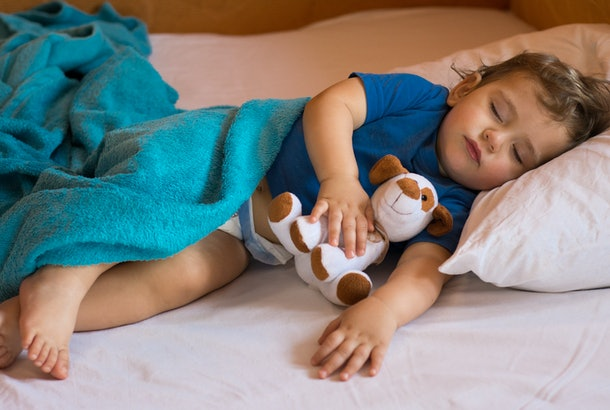 Cute baby boy sleeping on the bed at home with toy.