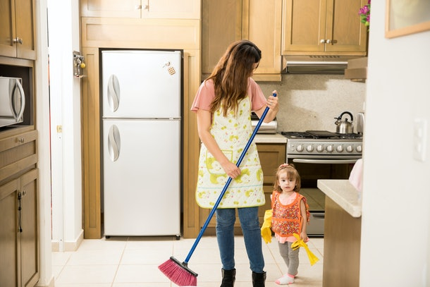 Adorable mother sweeping the floor with a broom while her gorgeous two year old girl follows her with gloves in the kitchen