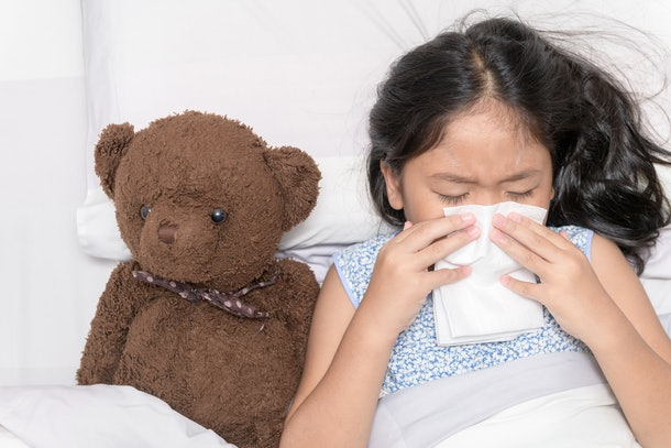 Sick little girl with the flu, blowing her nose into tissue lying with her teddy bear in her bed