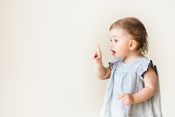 Baby girl pointing her finger, excited and emotional, isolated on white