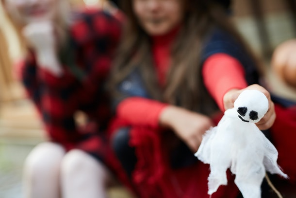 White toy ghost with black eyes held by little girl in halloween attire with her mom near by