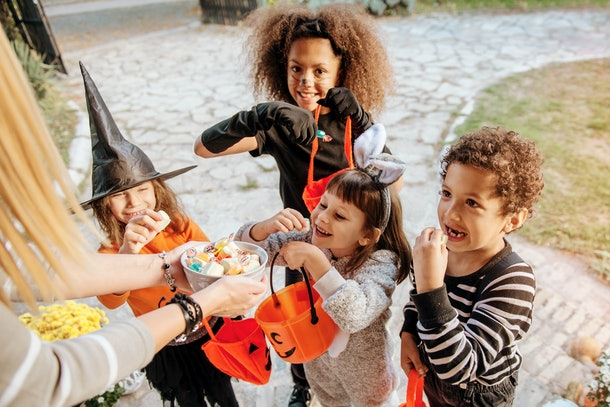 Children in Halloween costumes, trick or treating.