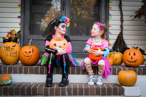 Halloween sisters sitting on porch trick or treating.