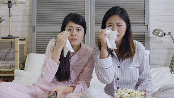 two best friends watch sad movie at home in bed crying