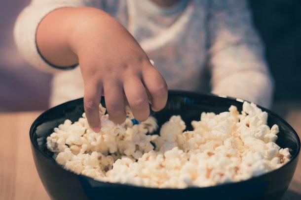 Close up of small kid eating popcorn.