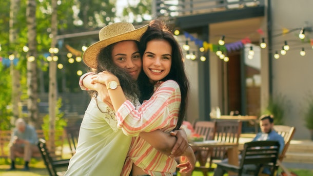 Portrait of Two Beautiful Girls Hugging and Smiling