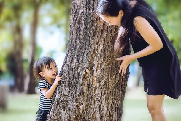 Recreation and development childhood with parental activity concept, Asian mom chasing a little girl in forest park with a game of Hide and Seek on vacation in emotion a happiness and excited.
