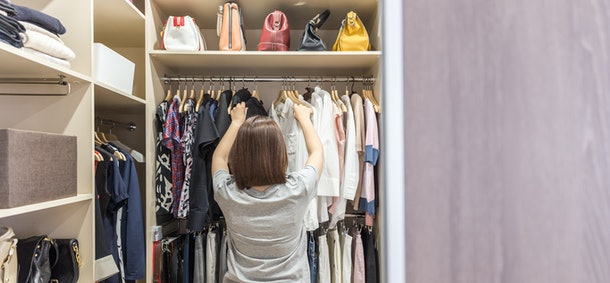 Woman in big walkin closet choosing clothes. modern wardrobe and dressing room with copy space