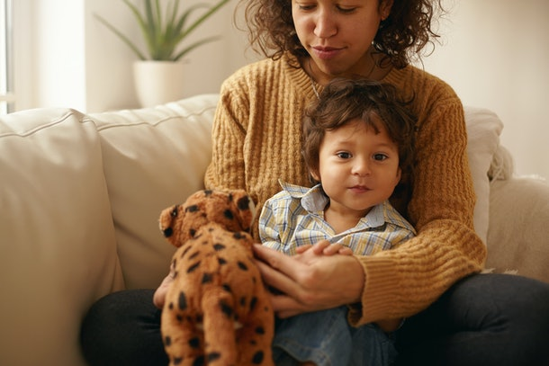 Indoor shot of happy caring young Latin woman sitting on sofa with adorable toddler on her lap playing with stuffed animal spending nice time together. Mother and son bonding in living room