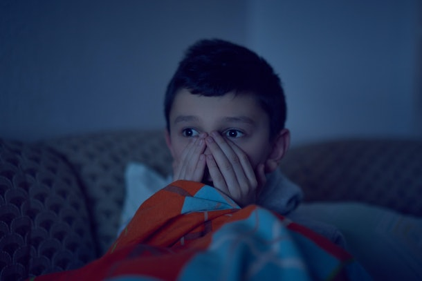 Scared child watching scary movie on tv, sitting on the couch at night