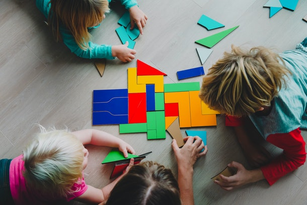 teacher and kids play with puzzle, doing tangram