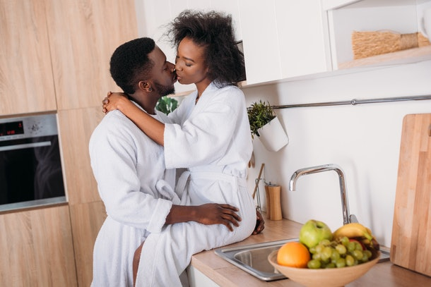 Young african american couple kissing in kitchen