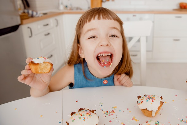 Close-up of color concentrates in tongue, in hand is a delicious cupcake, cooked by mom, fun and joy. The concept of Easter.