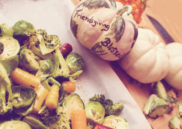 Friendsgiving Dinner preparing healthy vegetables for Thanksgiving with friends elevated view of carrots, broccoli and Brussels sprouts with pumpkins at home and words Friendsgiving and blessed
