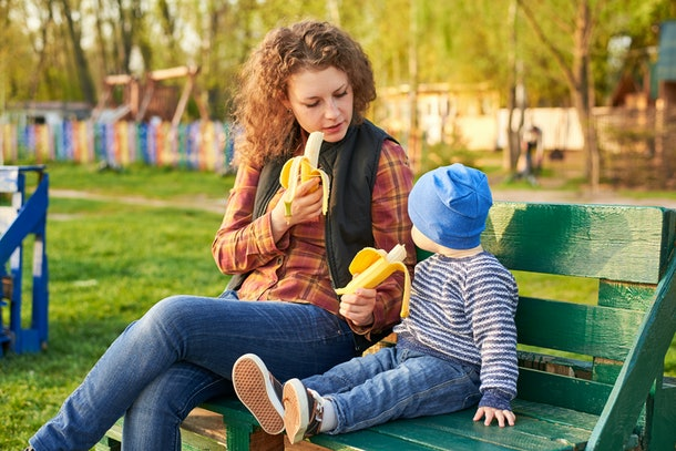 Mom eats and feeds her little son with banana on a bench in the park. Healthy eating concept