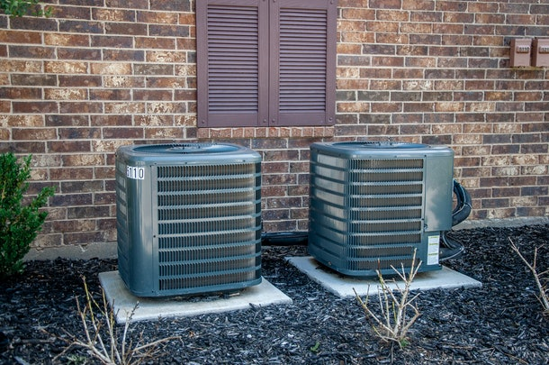 Air conditioning and heating units outside a brick building