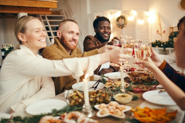 Multi-ethnic group of people raising glasses while celebrating Christmas with friends and family sitting at beautiful dinner table