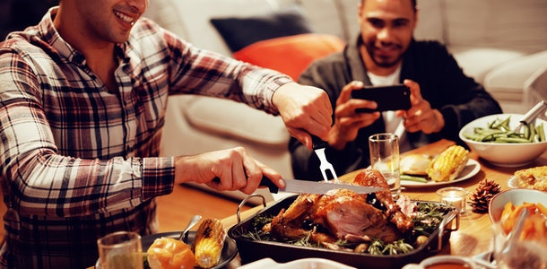 Front view of a young mixed race man sitting at a table for Thanksgiving dinner at home with friends carving the turkey, a young mixed race male friend taking a photo with his smartphone in the