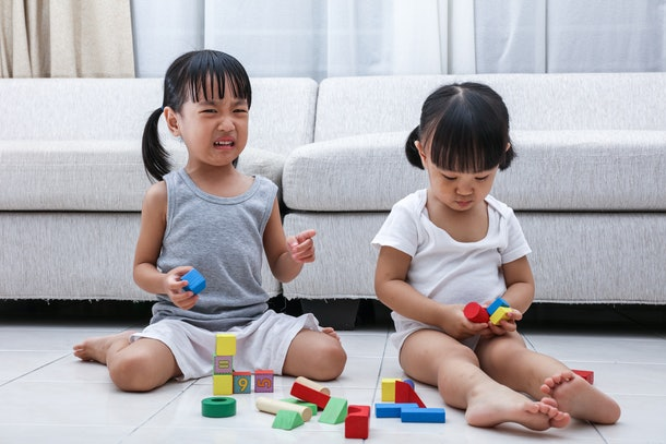 Asian Chinese little sisters struggle for blocks on the floor in the living room at home.