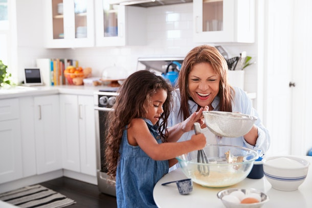 Young Hispanic girl making cake in the kitchen with her grandma, looking down