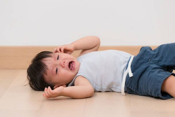 Asian little boy cry and lying on floor