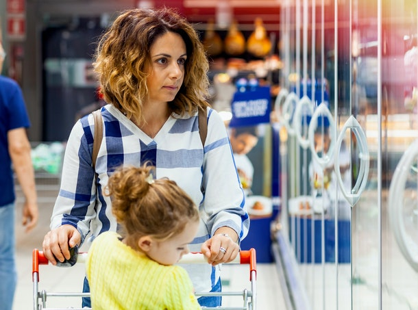Young Mother and daughter in the cart shopping for groceries in supermarket.