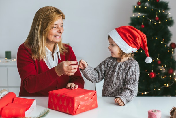 Gift wrapping. Little girl and her grandmother wrapping Christmas gift box together