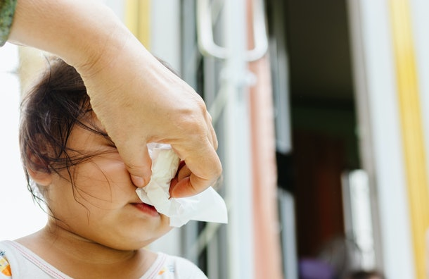 Mother helping to blow baby nose with paper tissue.