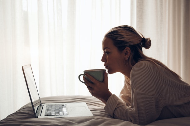 Silhouette of a young pretty woman working on laptop drinking coffee in the morning on the bed at home